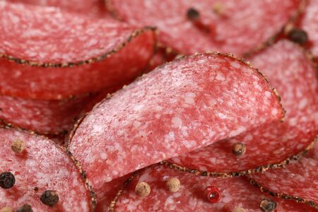Salami cut in slices with peppery edge decorated with pepper photo