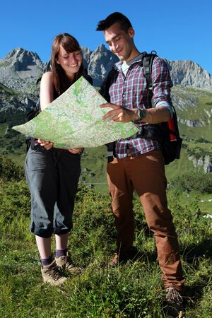 Young couple reading a map for orientation in the mountains. photo