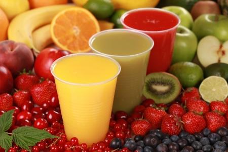 Bekers gevuld met verschillende soorten smoothies omgeven door verse vruchten