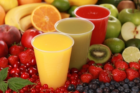 Cups filled with different kinds of smoothies surrounded by fresh fruits Stock Photo