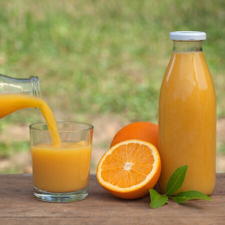 Fresh orange juice is being molded from a bottle into a glass Stock Photo - 15016546
