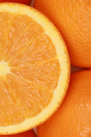 Closeup of a sliced fresh orange, decorated with more oranges photo