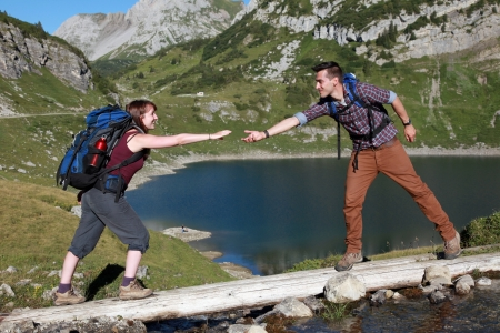 A young male hiker is helping a female hiker to cross a brook in the mountains Stock Photo