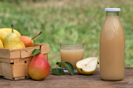 Fresh pear juice in a bottle and in a glass on a wooden table Stock Photo - 15016553