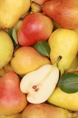 Groep van verse peren met bladeren vormen een achtergrond Stockfoto