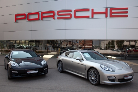 stuttgart: Stuttgart, Germany - September 4, 2012: Porsche Panamera sports cars in front of a Porsche dealer in Stuttgart Zuffenhausen. Porsche is a German company with investments in the luxury automotive industry.