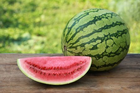 Slice of a watermelon and a whole one on a wooden table photo