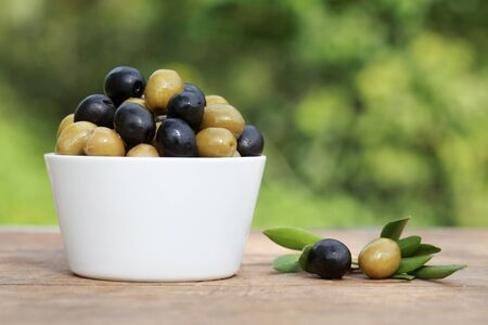 Green and black olives in a bowl on a wooden table with shallow depth of field photo