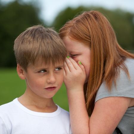 Girl whispering a secret into a boys ear photo
