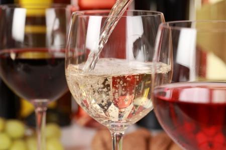 wine pouring: Vino bianco versando in un bicchiere di vino. Messa a fuoco selettiva sul vino bianco.