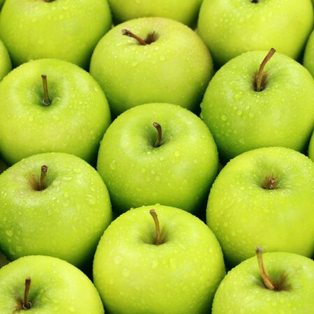 golden apple: Group of green apples with waterdrops forming a background Stock Photo