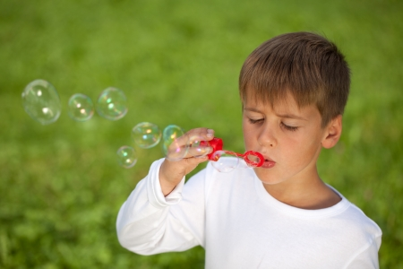 Little boy having fun with bubbles. Shallow depth of field. photo