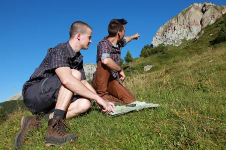 Two young backpackers reading a map and pointing on a mountain summit photo