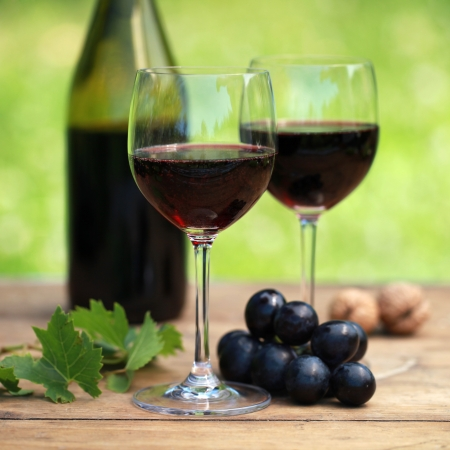 winetasting: Red wine on a wooden table in a bottle and two glasses. Selective focus on the glass in the foreground. Stock Photo