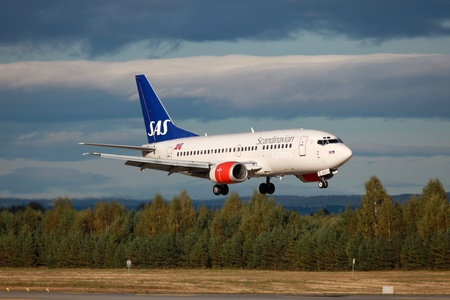 headquartered: Oslo, Norway - September 15, 2012: A SAS Scandinavian Airlines Boeing 737-500 with the registration LN-BUC approaches Oslo Airport (OSL) in Norway. SAS is the largest airline in Scandinavia and headquartered in Stockholm. SAS operates with 148 aircraft. I Editorial