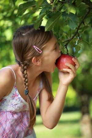 Meisje bijten in een appel van de boom. Ondiepe diepte van het veld. Stockfoto