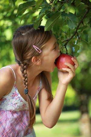 poco: Niña que muerde una manzana del árbol. Poca profundidad de campo.