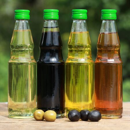 Collection of cooking oil in small bottles on a wooden table photo