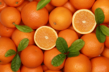 Collection of fresh oranges with leaves forming a background