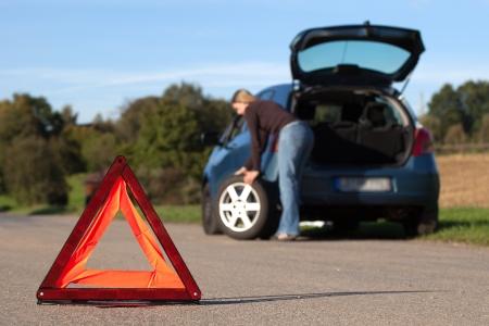 Uitgesplitst auto op een weg met een rode gevarendriehoek