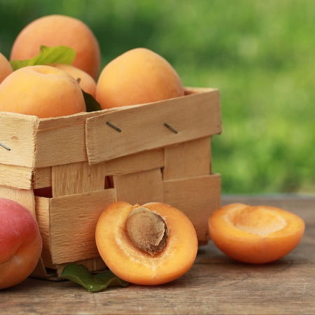 Apricots with leaves in a wooden box on a wooden table with green background  Stock Photo - 15805141