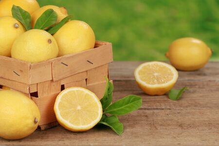 Lemons with leaves in a wooden box on a table with green background  Stock Photo - 16057600
