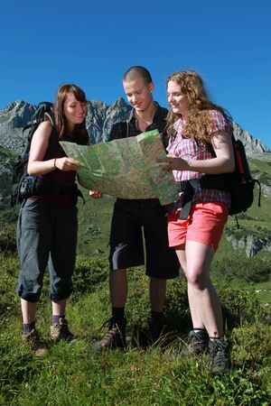 Young people reading a map for orientation in the mountains. photo