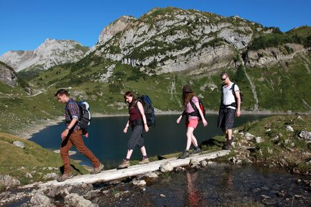 Young people cross a brook in the mountains photo