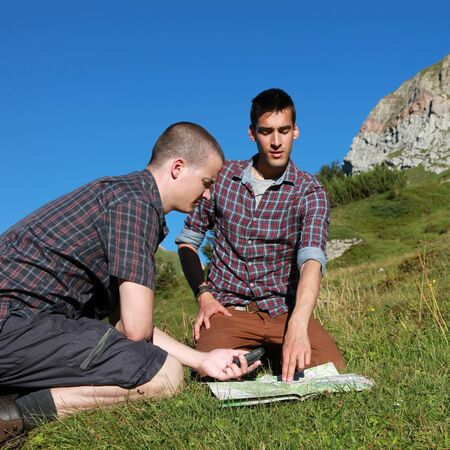 freetime activity: Two young backpackers reading a map in the mountains