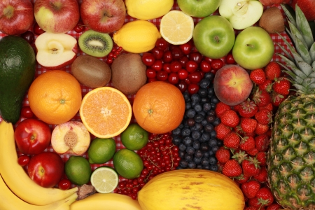 Fruit background with oranges, lemons, bananas, apples and strawberries
