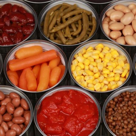 Verschillende soorten groenten zoals maïs en wortelen in blikken Stockfoto