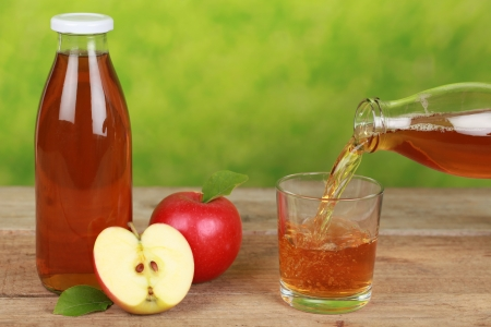 Fresh apple juice is pouring from a bottle into a glass Stock Photo - 16213527