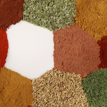 Colorful spices and herbs like salt, paprika, curry and caraway forming a background photo