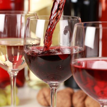 Verse rode wijn gieten in een wijnglas. Selectieve focus op de rode wijn.