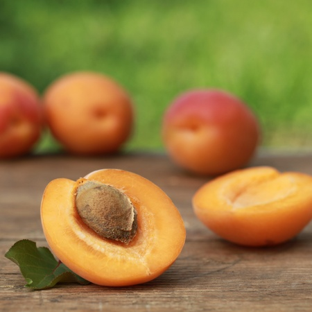 Ripe apricots with leaves on a wooden table with green background  Stock Photo - 16213474
