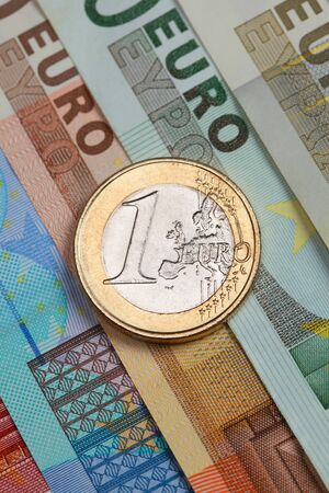 One Euro coin on Euro banknotes forming a money background photo