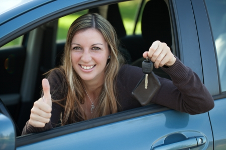 A happy driver leaning out of the window and showing the car key Stock Photo - 16128852