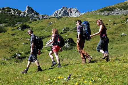 Group of young backpackers hiking in the mountains photo