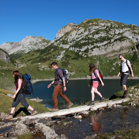 Young people cross a brook in the mountains during a hiking tour photo