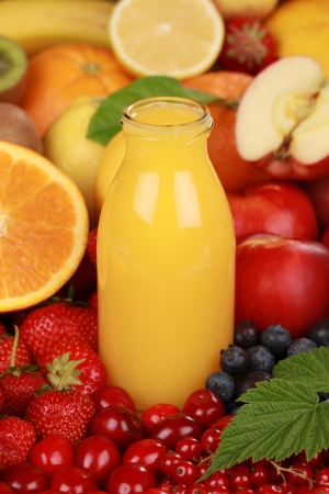 Orange juice in a bottle surrounded by fresh fruits Stock Photo - 16481613