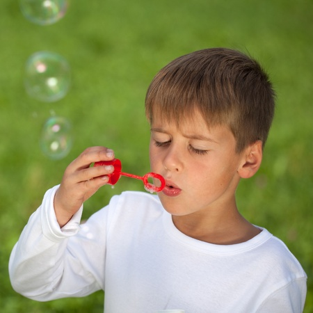 Boy having fun with bubbles on a green meadow. Shallow depth of field. photo