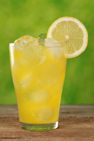 Cold lemonade in a glass with ice cubes, served with a lemon