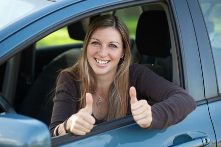 Een gelukkig vrouwelijke bestuurder leunt uit het raam en het tonen van beide duimen omhoog Stockfoto
