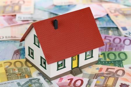 Symbool voor huis financiering met een huis op Eurobiljetten