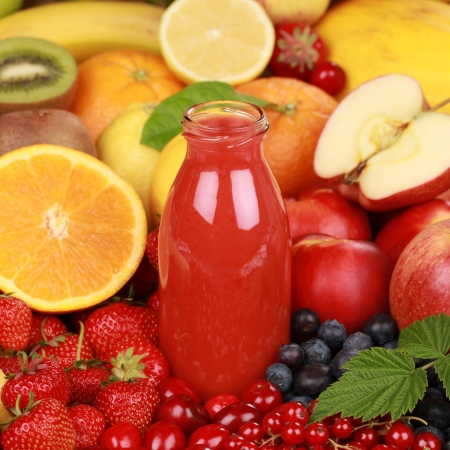 Freshly squeezed juice from red fruits such as apples, cherries and strawberries in a bottle Stock Photo - 16690709