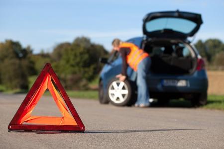 Reifenwechsel auf einem kaputten Auto mit einem roten Warndreieck Standard-Bild