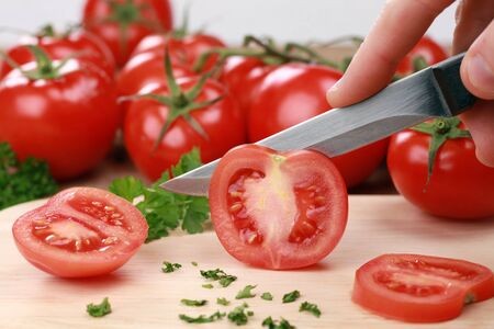 knife tomato: Preparing food: sliced tomatoes on a kitchen board Stock Photo