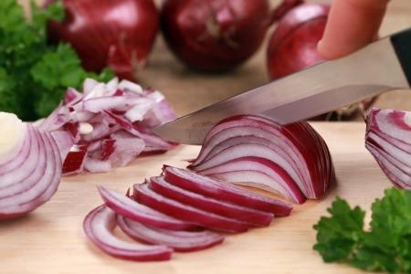 onions: Preparación de los alimentos: corte las cebollas en una placa de cocina Foto de archivo