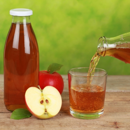 Apple juice is pouring from a bottle into a glass Stock Photo - 16887216