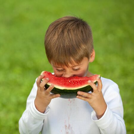 Small child eating a fresh watermelon on a green meadow with blurred background. photo